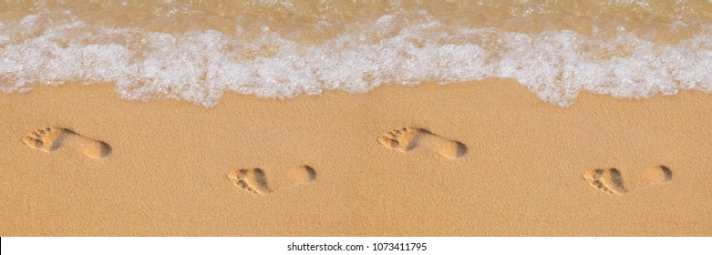 Texture background Footprints of human feet on the sand near the water on the beach
