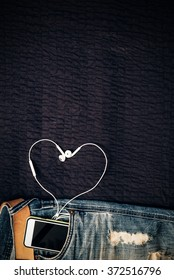 Texture background of jeans , belt detail with mobilephone and earphone as heart shape