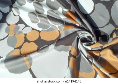 Texture, background, pattern. Abstract pattern on a silk fabric, white yellow brown circles
