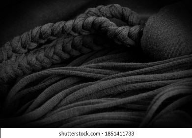 Texture, background, pattern. Fabric in black braids. Knitted knitted background with embossed pattern. Braids in knitting.