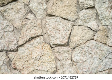 Texture, background, pattern. Granite stone. Texture of gray granite. Outside wall of uneven stones. White and pale red stones. The stone texture is rough and rusty