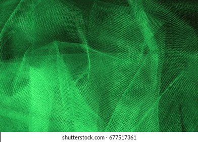 Texture, background, pattern. Green, salad color of silk fabric. Green fabric texture. Close up view of green fabric texture and background. Abstract background and texture for designers.