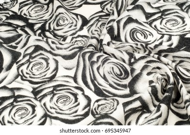 Texture, background, pattern. A woolen scarf, black and white, roses are drawn on a scarf. Woolen black and white fabric