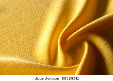 Texture, background, pattern. Yellow jacquard fabric. Providing both a texture and a thin structure, they demonstrate a quilted hand in a wave of geometric design. Jacquard has a transparent opacity