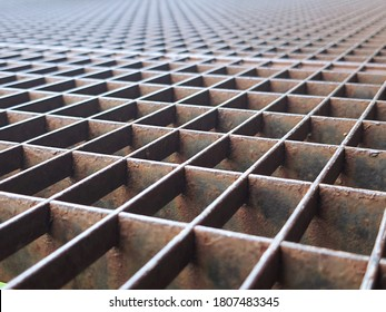Texture and background of protective street ground metal iron grid or stainless steel grating in perspective