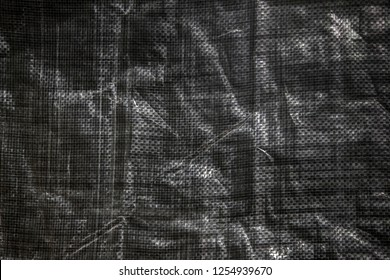 The texture of black crumpled polyethylene woven fabric. Abstract dark background of synthetic polypropylene or polyethylene (PP, PE) material which used as outdoor tarpaulin