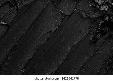 Texture of black crushed eyeliner or black acrylic paint isolated on white background