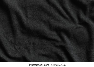 Texture of black fleece, soft napped insulating fabric made from polyester, wavy pattern