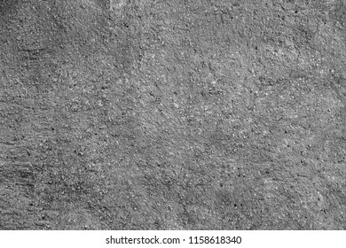 Texture of a black-and-white wall with plaster, cracks, felling, stains and granularity.