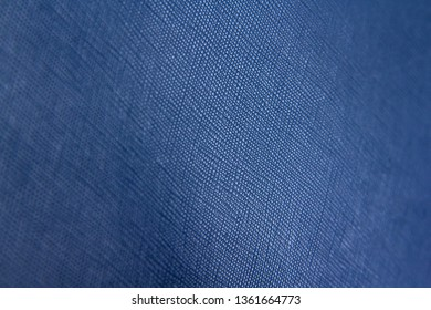 Texture of blue natural leather with lines and bumps. With blurring around the edges. Backdrop or background.