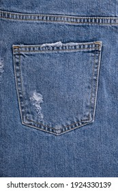 Texture of blue torn jeans. Back pockets jeans