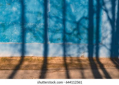 The texture of the blue wall with peeling old paint, with shadows and tree branches, with a yellow harmonious stripe of earth. For design, backgrounds, wallpapers, covers, advertising, textures.