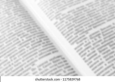 Texture of a blurry text in an open periodical or a book for the background. Diagonal image of the magazine. Words or information for the template. Black and white colors.