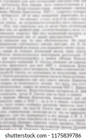 Texture of a blurry text in an open textbook or a book for the background. Diagonal image of the magazine. Words or information for the template. Black and white colors.