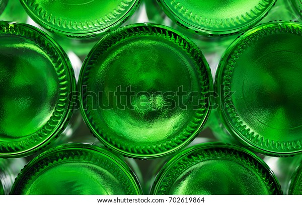 The texture from the bottom of the green beers from the beer lit with bright light.  Wall of back-lit green bottles. glass background, glass texture.Bottoms of green wine bottles on a white background