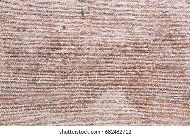 Texture of brick fortress wall with grass sticking out from its cracks.