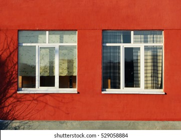 texture of a bright brick-colored plaster and windows at the clinic