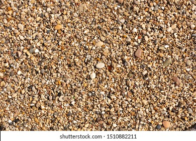 texture of bright and colored pebbles, wet by the waves of the beach