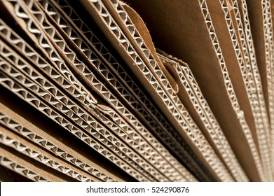 Texture of brown cardboard side. Folded cardboard boxes. Wavy paper texture on sunlight.