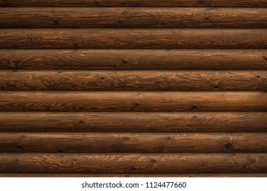 Texture of the brown textured log wall of a wooden blockhouse