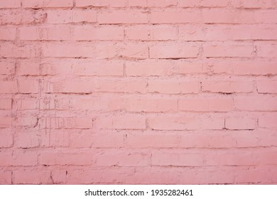 The texture of the building facade of a brick wall from rows of bricks painted in pink color