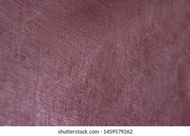 Texture of burgundy natural leather with lines and bumps. With blurring around the edges. Backdrop or background.