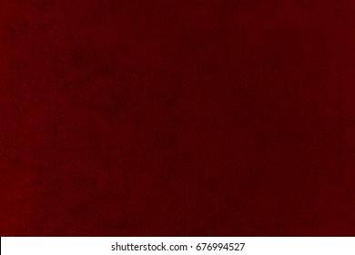 The texture of the  burgundy velvet. The background of burgundy cloth. Background of  burgundy velvet.