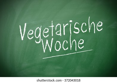 Texture of a chalkboard with the German words vegetarian week, Healthy eating concept