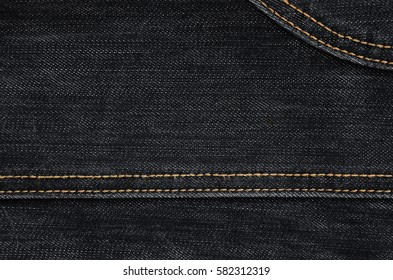 The texture of classic black denim cloth. Dark jeans background with thin seams