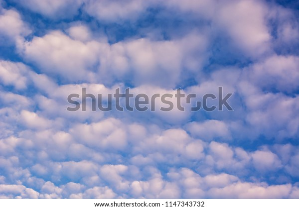 Texture of clouds on blue sky illuminated by sunlight