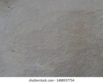 Texture of a concrete wall with cracks and scratches which can be used as a background. Stone wall for use as a background.