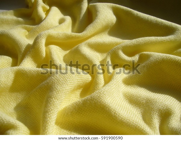 The texture of the cotton fabric. The yellow cloth. Yellow jersey.