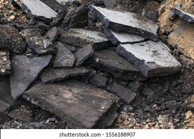 Texture of cracked asphalt. Concrete replacement outdoors. City maintenance. Black structure. Pile of plates. Construction garbage.