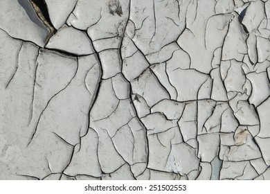 The texture of cracked white paint on a wooden wall