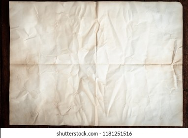 Texture of crumpled folded vintage paper background with spot and stain on wooden table