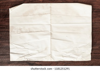 Texture of crumpled vintage paper background with spot and stain on wooden table