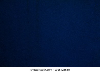 texture of a dark blue wall covered with volumetric plaster, space for text, space for copy