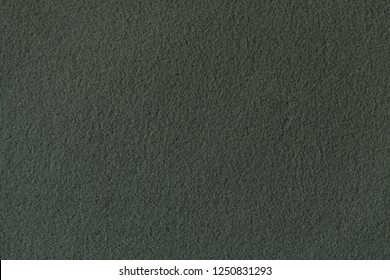 Texture of dark green fleece, soft napped insulating fabric made from polyester