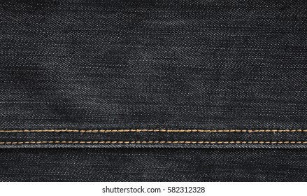 The texture of denim in classic monochrome tone with bright seams of thin fabric. The background image on the production of rigid denim clothing