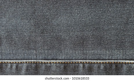 The texture of the denim fabric is gray, with a horizontal seam