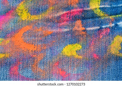 The texture of denim with strokes of fluorescent gouache color paint. Abstract background jeans