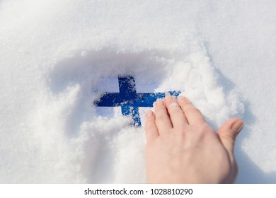 The texture of the flag of Finland in the snowdrift, a female hand digs a snow-covered flag.