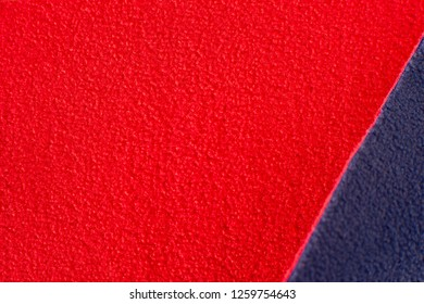 Texture of fleece fabric. Red and blue fleece fabric creates a textural background. Fabric fleece for sewing and design of fashionable clothes and objects.