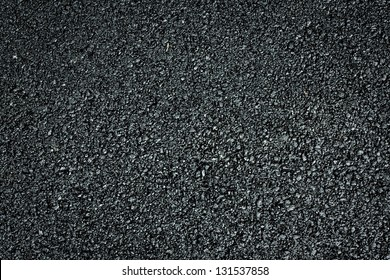 The texture of fresh asphalt lined up close. Pavement