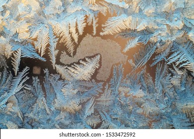 Texture of frosty patterns. Winter frosty blue patterns on the glass. Icy, frosty pattern on the window glass. Background for christmas and new year. Macro. Close up