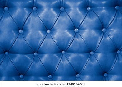 Texture of genuine blue leather upholstered furniture. Decorative background of genuine quilted leather capitone texture