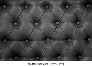Texture of genuine dark grey leather upholstered furniture. Decorative background of genuine quilted leather capitone texture