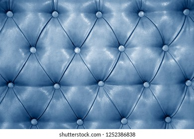 Texture of genuine light blue leather upholstered furniture. Decorative background of genuine quilted leather capitone texture
