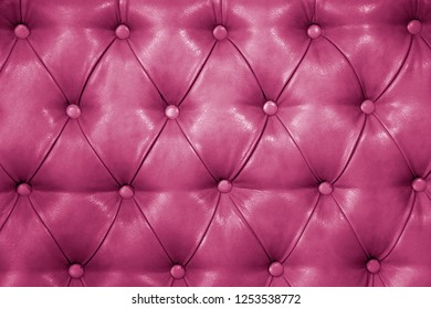 Texture of genuine pink leather upholstered furniture. Decorative background of genuine quilted leather capitone texture