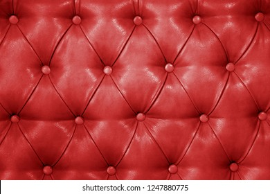 Texture of genuine red leather upholstered furniture. Decorative background of genuine quilted leather capitone texture